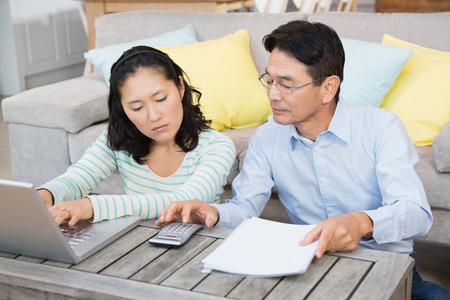 credit crunch: Worried couple checking bills in the living room