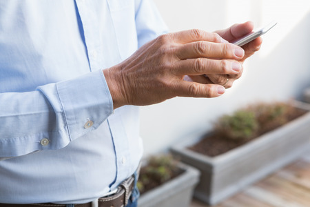 mid section: Mid section of man using smartphone at home in the garden Stock Photo