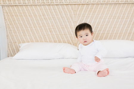 baby sit: Cute baby on bed looking at the camera
