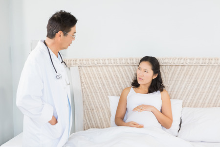 gynaecology: Doctor visiting pregnant woman in bedroom