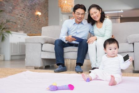 convivencia familiar: Padres felices que miran a su hija bebé en la sala de estar