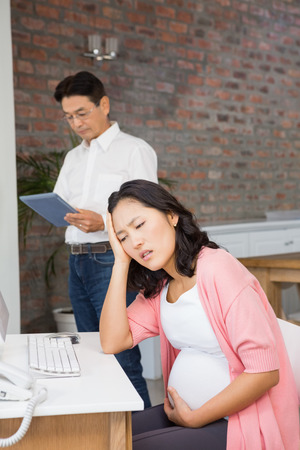 seniors suffering painful illness: Suffering pregnant woman sitting at desk at home while husband is using tablet