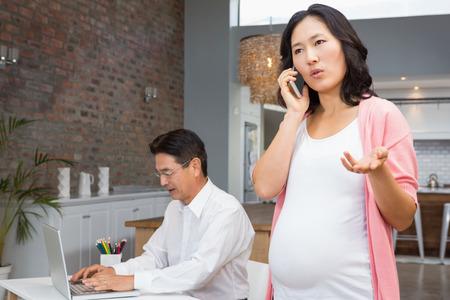 trabajando en casa: mujer embarazada en una llamada de teléfono sonriente en su casa mientras que el marido trabaja en la computadora portátil
