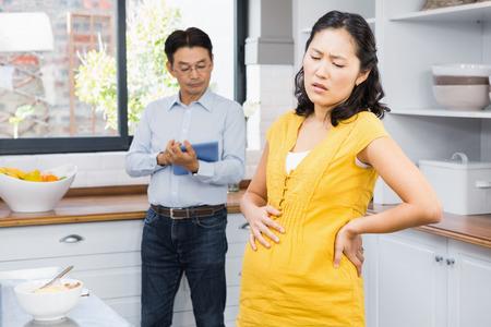 back ache: Pregnant woman with back ache in the ktichen Stock Photo