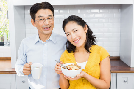 expectant arms: Portrait of happy expectant couple in the kitchen in morning