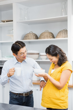 expectant arms: Happy expectant couple in the kitchen having breakfast Stock Photo