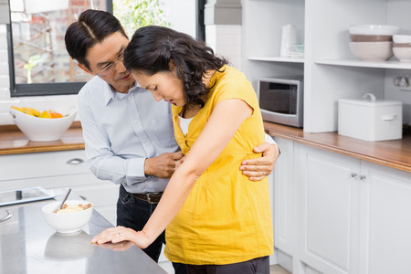 taking a wife: Husband taking care of his suffering pregnant wife in the kitchen