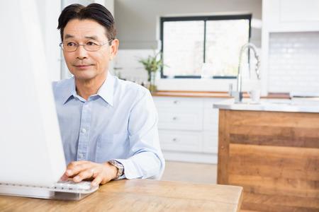 senior men: Concentrated man using computer at home