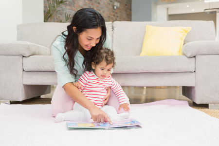 mixed race woman: Happy mother with her baby looking at a book on the carpet in living room Stock Photo