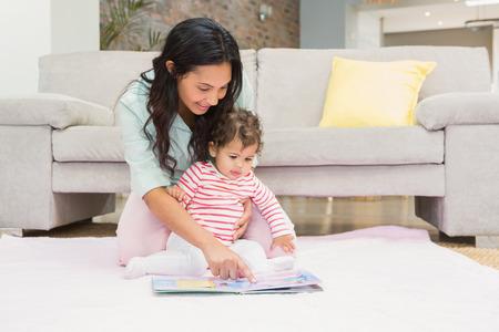 bebe sentado: Madre feliz con su bebé mirando un libro en la alfombra en la sala de estar