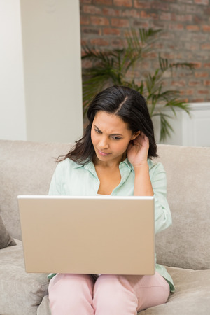 unsmiling: Unsmiling brunette using laptop on the sofa