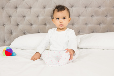looking around: Cute baby sitting on bed looking around Stock Photo