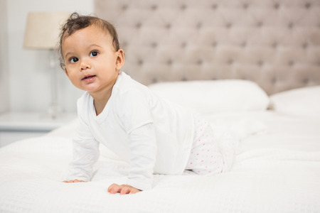 looking around: Smiling baby on bed looking around Stock Photo