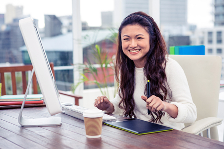 classy woman: Smiling Asian woman using digital board and computer in office