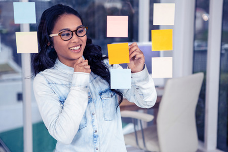 glass wall: Asian woman looking at sticky notes on glass wall