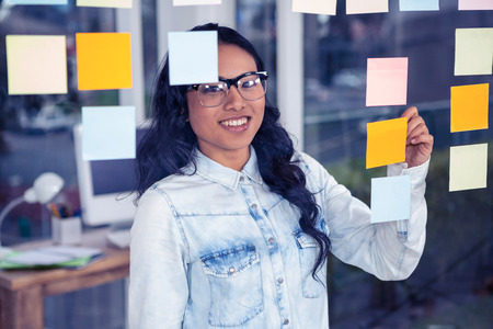 glass wall: Asian woman writing on sticky notes on glass wall Stock Photo