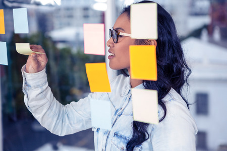 removing: Asian woman removing sticky note by glass wall Stock Photo