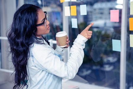 glass wall: Asian woman pointing sticky note on glass wall