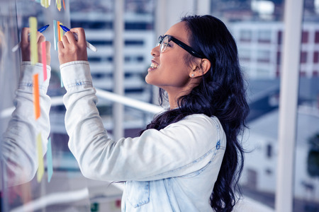 sticky notes: Asian woman writing on sticky notes on glass wall Stock Photo