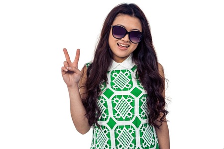 Asian woman with sunglasses making peace sign on white screen