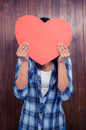 woman hiding: Woman hiding her face behind paper heart against wooden wall