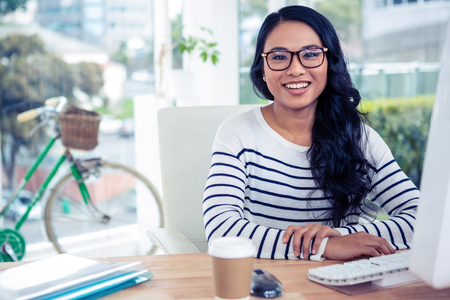 Smiling Asian woman sitting at desk posing for camera in office Stock Photo