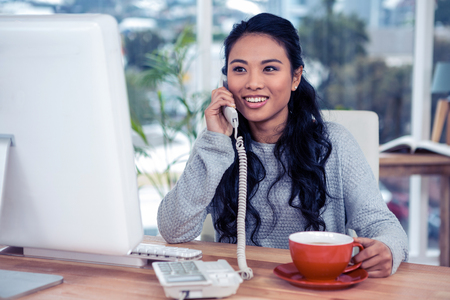 Smiling Asian woman on phone call holding mug in office Banco de Imagens