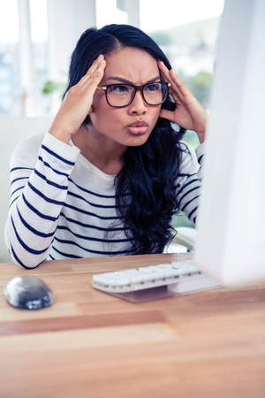 frowning: Frowning Asian woman looking at computer monitor with hands on head in office Stock Photo