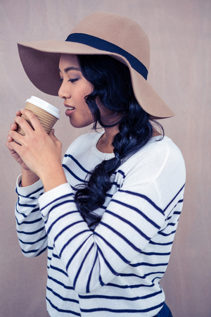 disposable cup: Attractive Asian woman with hat holding disposable cup