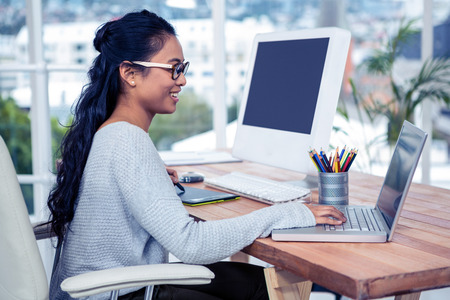 asian women: Smiling Asian woman using laptop and digital board in office Stock Photo