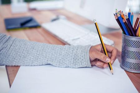 Womans mano con lápiz de dibujo en una hoja blanca en la oficina