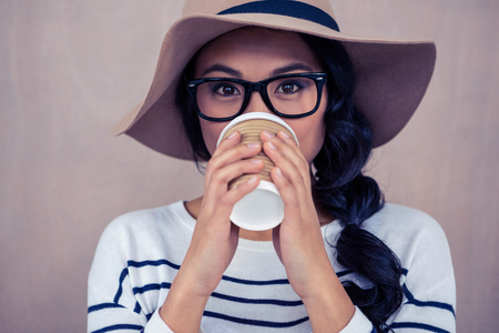 Donna asiatica attraente che beve da tazza usa e guarda alla macchina fotografica