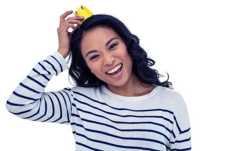 fake smile: Smiling Asian woman with paper crown on white screen