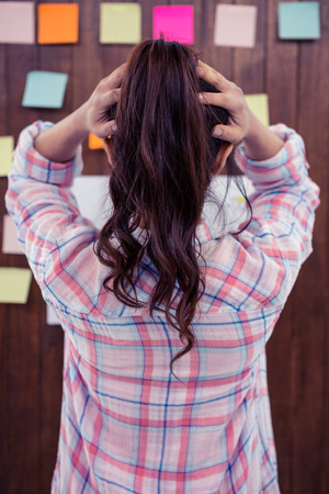 sticky hands: Rear view of brunette with hands on hair in front of sticky notes on wooden wall