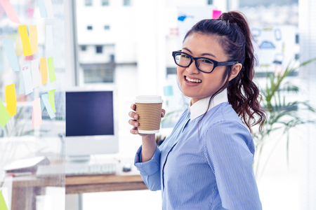 disposable cup: Businesswoman holding disposable cup and looking at wall with notes in office