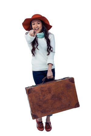 pre adult: Smiling Asian woman holding luggage pointing the camera on white screen