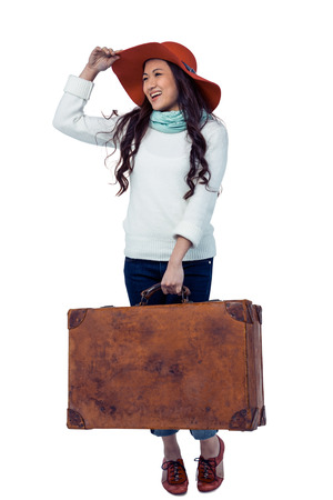 pre adult: Smiling Asian woman holding luggage holding hat on white screen