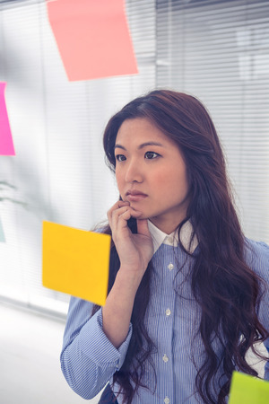 sticky notes: Asian businesswoman using sticky notes on wall in office Stock Photo