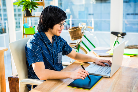 laptop keyboard: Smiling hipster businessman using laptop and graphic tablet in office Stock Photo