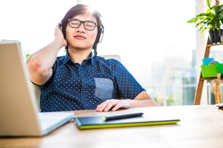 listening: Smiling asian businessman listening to music in office Stock Photo