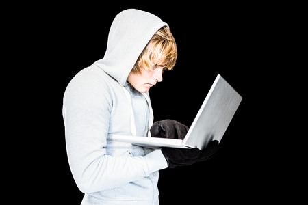 intruding: Focused man with hoodie typing on laptop with black background