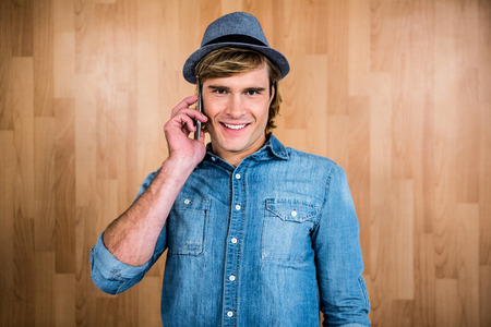 technologic: Smiling blonde hipster phone calling against wooden wall