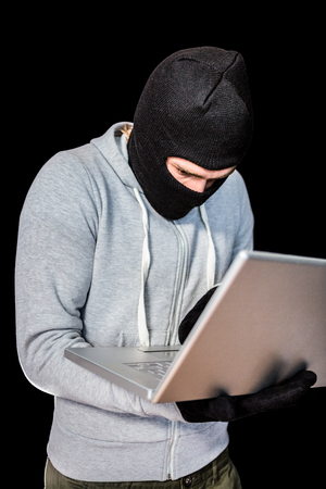 intruding: Focused thief with hood typing on laptop with black background