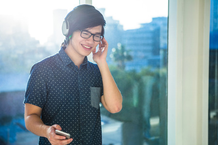 man office: Smiling asian businessman listening to music in office Stock Photo