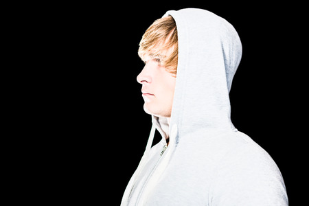 intruding: Side view of serious man looking away with black background Stock Photo