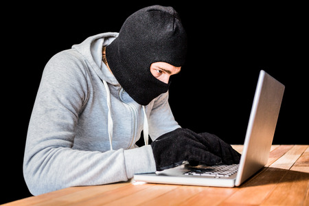 robbing: Focused thief with hood typing on laptop with black background