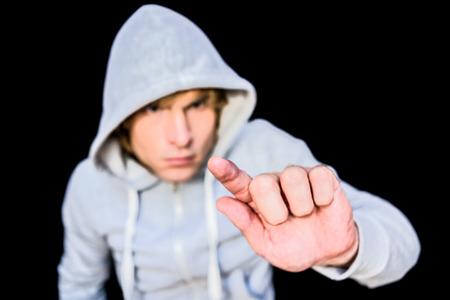 intruding: Man in hood jacket on black background