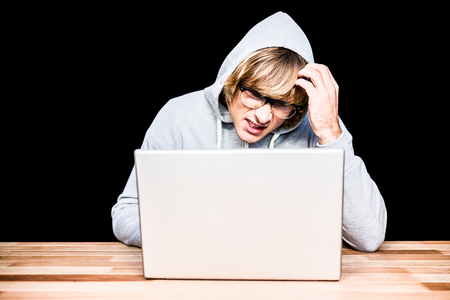 intruding: Man in hood jacket hacking a laptop on black background