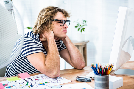troubled: Troubled hipster businessman sitting in his office and holding his neck Stock Photo