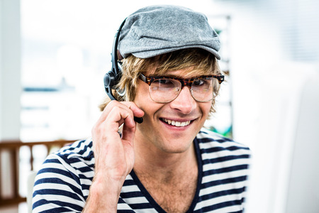 cool guy: Smiling hipster businessman using headset in his office